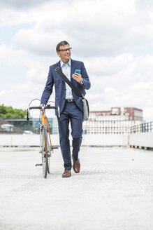Businessman pushing bike while talking on the phone - UUF005331