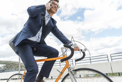 Businessman riding bicycle, talking on the phone - UUF005338