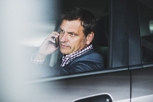 Mature businessman using smart phone in the car - UUF005251