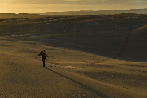 South Australia, man with tripod and camera walking through sand dunes at twilight - TOVF000022