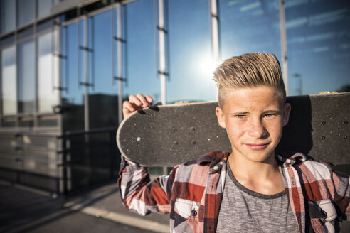 Portrait of teenager holding skateboard - AIF000018