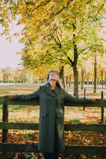 Woman leaning on wooden fence in an autumnal park - CHAF001122
