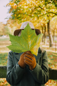Woman hiding her face behind an  autumn leaf - CHAF001123