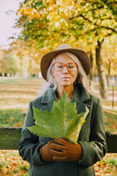 Portrait of woman with closed eyes oman holding an autumn leaf in her hands - CHAF001124