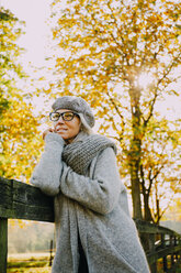 Portrait of woman wearing grey knitwear in an autumnal park - CHAF001127