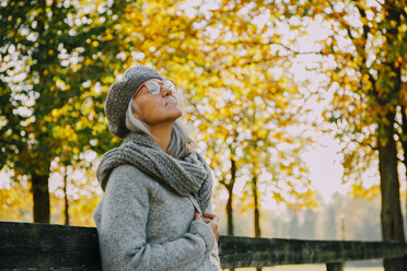 Woman wwith closed eyes in an autumnal park - CHAF001128