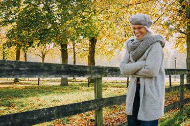 Woman enjoying day at autumnal park - CHAF001130