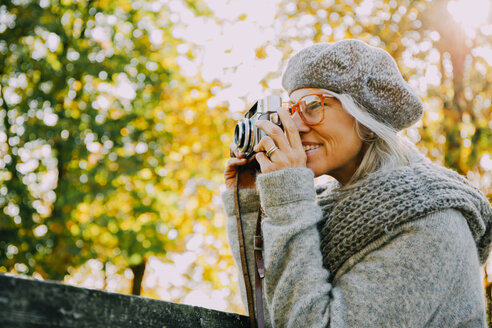 Woman taking pictures with an old camera in an autumnal park - CHAF001132