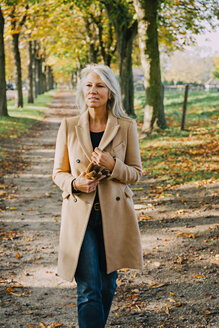 Portrait of woman walking in autumnal park - CHAF001140