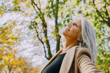 Happy woman in autumnal park looking up - CHAF001141