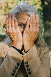 Portrait of woman peeking through her hands - CHAF001144