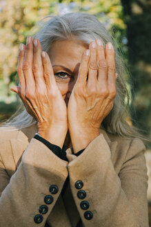Portrait of woman peeking through her hands - CHAF001144