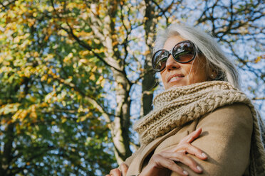 Portrait of smiling woman wearing scarf and sunglasses in a park - CHAF001145