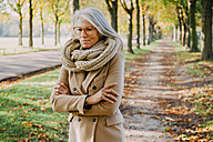 Portrait of woman wearing scarf and glasses walking in autumnal park - CHAF001147