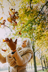 Woman throwing autum leaves in the air - CHAF001150