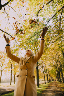 Woman throwing autum leaves in the air - CHAF001151