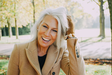 Portrait of laughing woman with hands in her hair in autumnal park - CHAF001152