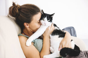 Woman sitting on the sofa hugging her cat - GEMF000306