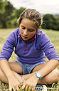 Girl sitting on a meadow looking down - MGOF000410