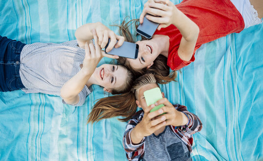 Three teenage friends with smartphones lying on blanket - AIF000065