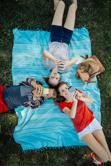 Three teenage friends with smartphones lying on blanket - AIF000067