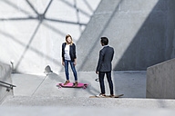 Two business people standing on skateboards in modern architecture - FMKF001737