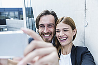 Portrait of two laughing business people taking a selfie with smartphone - FMKF001743