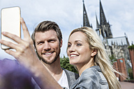 Germany, Cologne, young couple taking a selfie with smartphone - FMKF001761