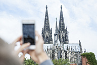 Germany, Cologne, young woman taking a picture of Cologne Cathedral with smartphone - FMKF001763