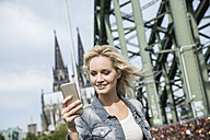 Germany, Cologne, young woman with smartphone on Hohenzollern Bridge - FMKF001766