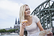 Germany, Cologne, portrait of young woman with bagel and city map - FMKF001769