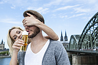 Germany, Cologne, young man tasting Koelsch while his girlfriend covering his eyes - FMKF001772