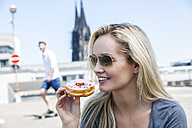 Germany, Cologne, portrait of young woman eating bagel - FMKF001780