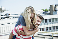 Germany, Cologne, young man giving his girlfriend a piggy back - FMKF001783