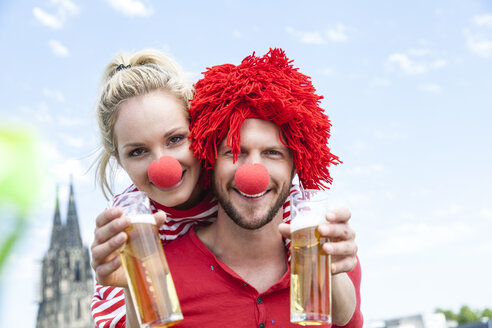 Germany, Cologne, young couple celebrating carnival dressed up as clowns - FMKF001789