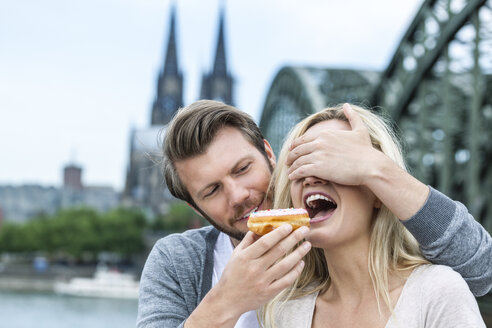 Germany, Cologne, young woman tasting a bagel while her boyfriend covering her eyes - FMKF001791