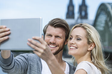 Germany, Cologne, portrait of smiling young couple taking a selfie with digital tablet - FMKF001794