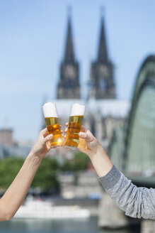Germany, Cologne, couple toasting with Koelsch glasses - FMKF001797
