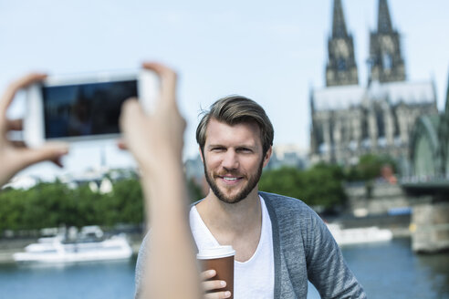 Germany, Cologne, young woman taking a picture of her boyfriend with smartphone - FMKF001802