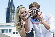 Germany, Cologne, young couple taking a picture with camera - FMKF001817
