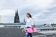 Germany, Cologne, young woman with pink skateboard on roof terrace - FMKF001822