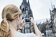 Germany, Cologne, young woman taking a picture of Cologne Cathedral with smartphone - FMKF001806