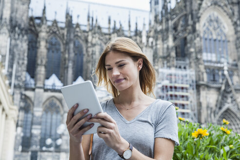 Germany, Cologne, portrait of young woman with mini tablet in front of Cologne Cathedral - FMKF001808