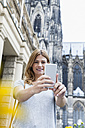 Germany, Cologne, portrait of young woman taking a selfie with smartphone - FMKF001811
