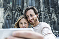 Germany, Cologne, portrait of young couple taking a selfie in front of Cologne Cathedral - FMKF001826