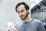 Portrait of young man looking at his smartphone - FMKF001829