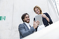 Two smiling business people looking at digital tablet - FMKF001834