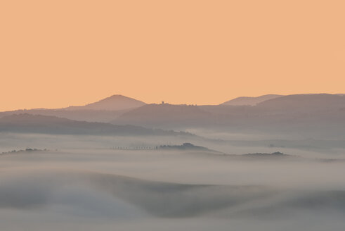 Italy, Tuscany, Val d'Orcia, view to rolling landscape at sunrise in the fog - LOMF000044