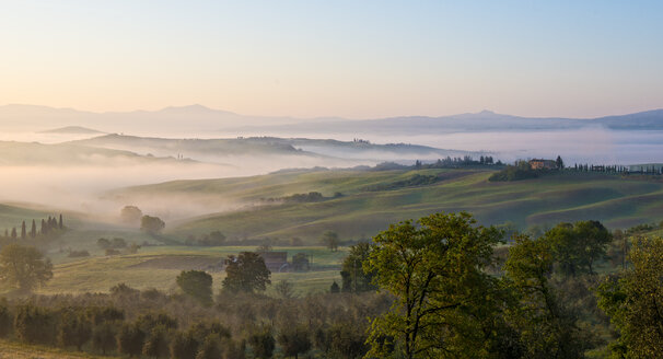 Italy, Tuscany, Val d'Orcia, view to rolling landscape at sunrise in the fog - LOMF000042
