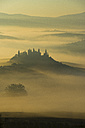 Italy, Tuscany, San Quirico d'Orcia, view to rolling landscape at sunrise in the fog - LOMF000040
